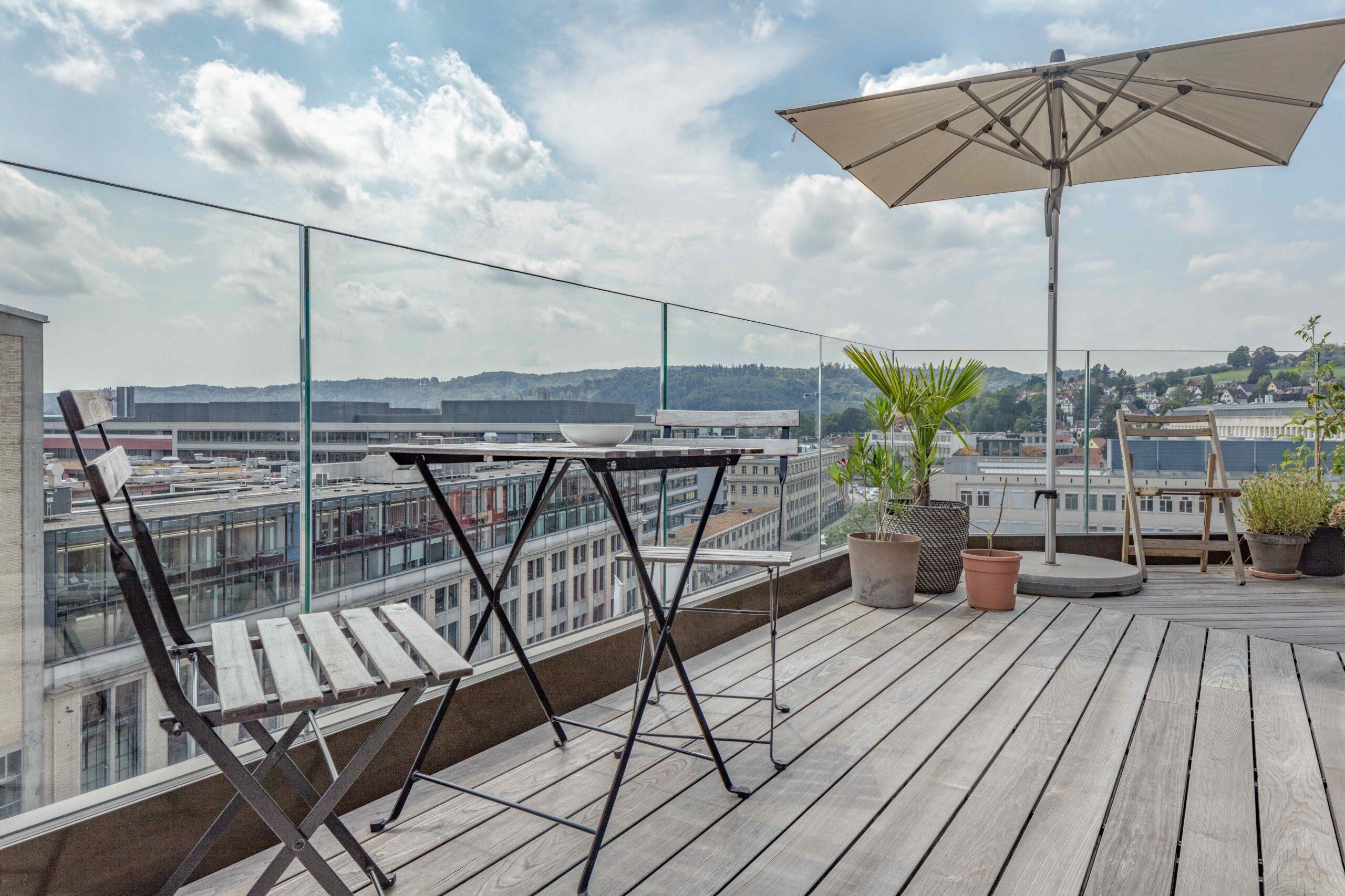 Dachterrasse mit Ganzglasgeländern und Stadtblick und Sitzmöglichkeit